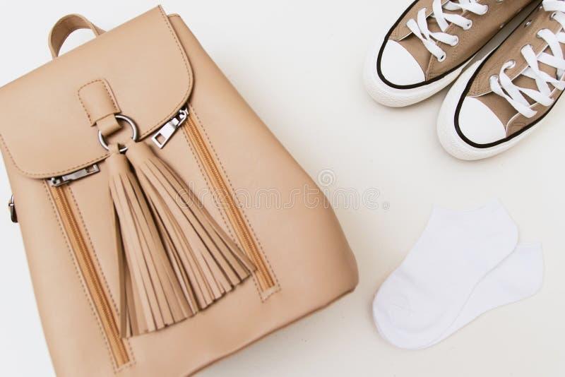 在棕色运动鞋的顶视图,米黄背包,在淡色背景的白色袜子 库存图片