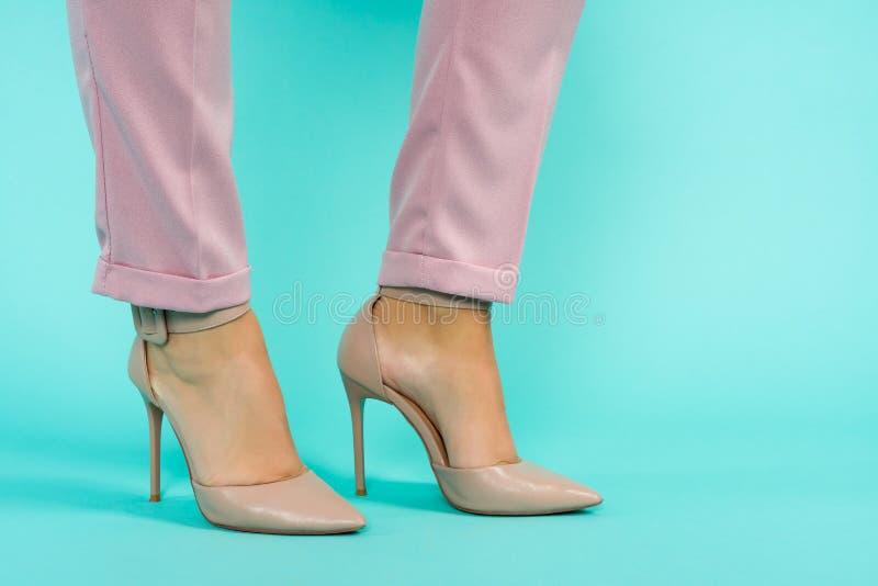 在棕色高跟鞋鞋子的性感的腿在蓝色背景 免版税图库摄影