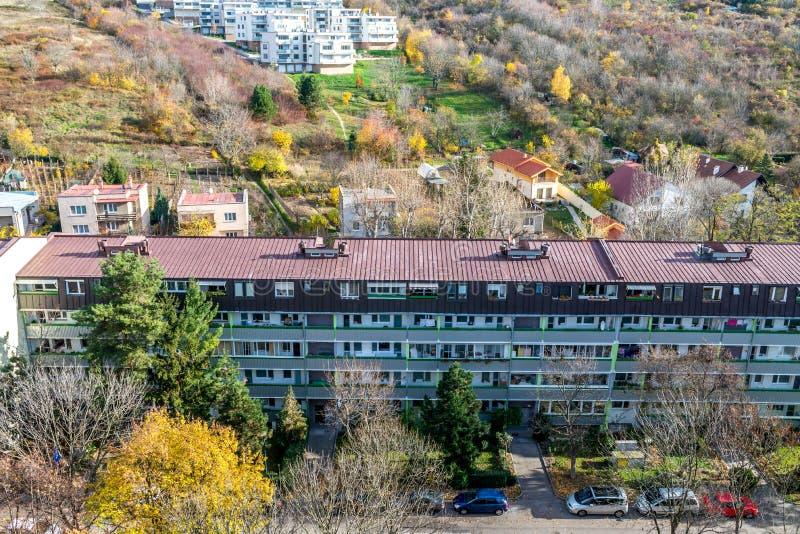 在森林和家庭房子附近的低预制房子在布拉索夫斯洛伐克 库存照片