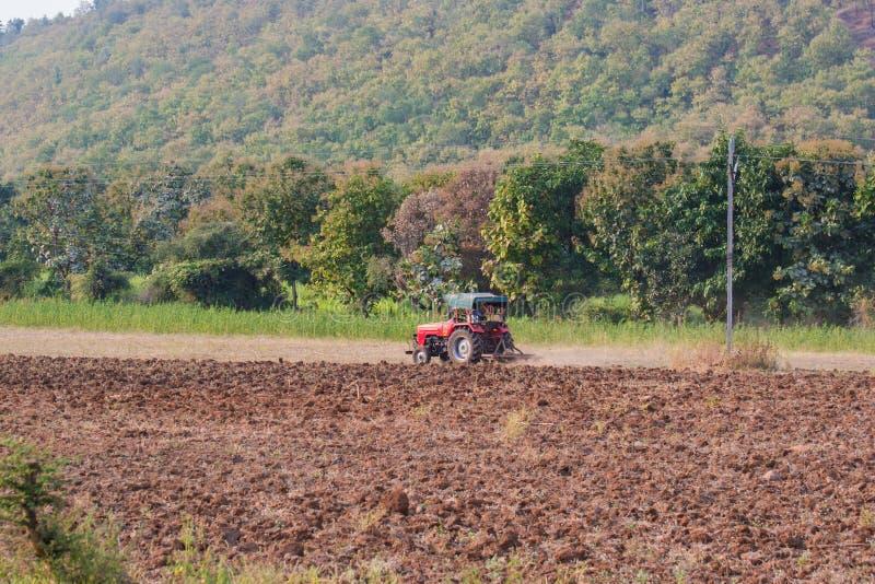 在森林土地的拖拉机耕的农业领域 免版税库存图片