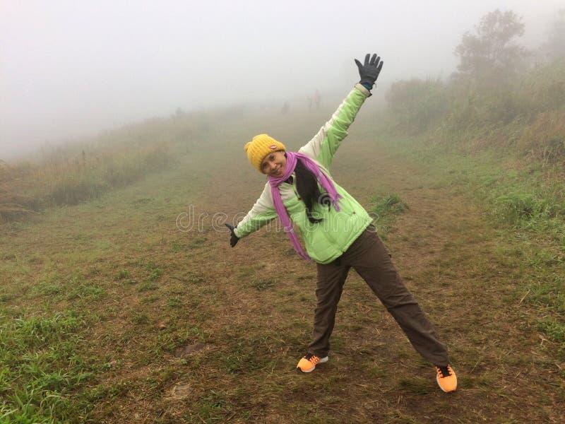 在森林山的妇女愉快的雾 库存照片