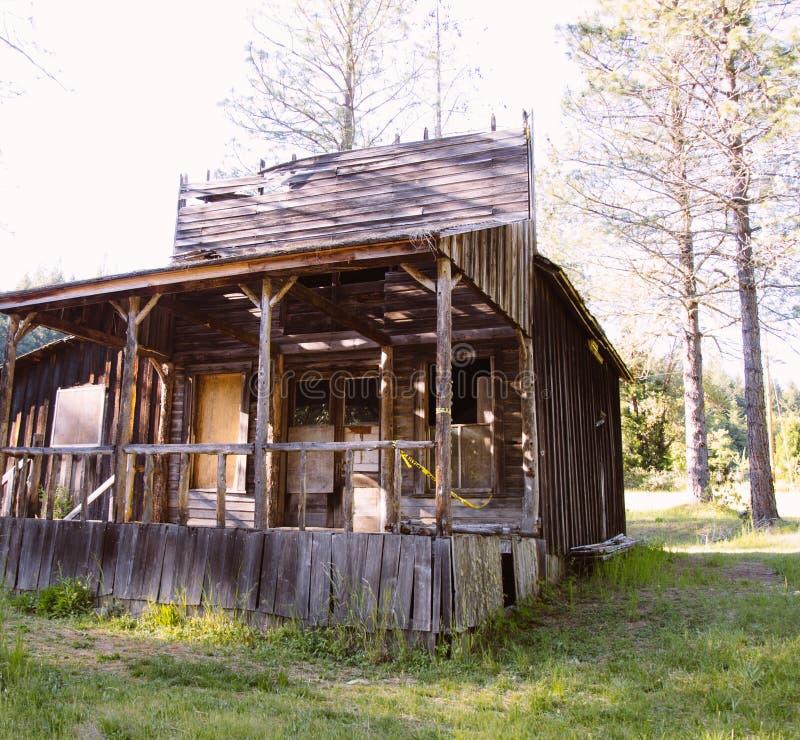 在森林建造的被放弃的老木房子 免版税库存照片