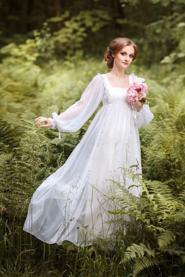 在森林边缘的女孩一件长的白色礼服的 图库摄影