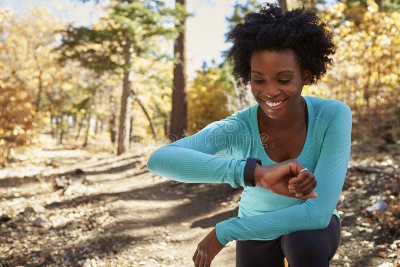 在森林里检查smartwatch和微笑的年轻黑人妇女 免版税库存图片