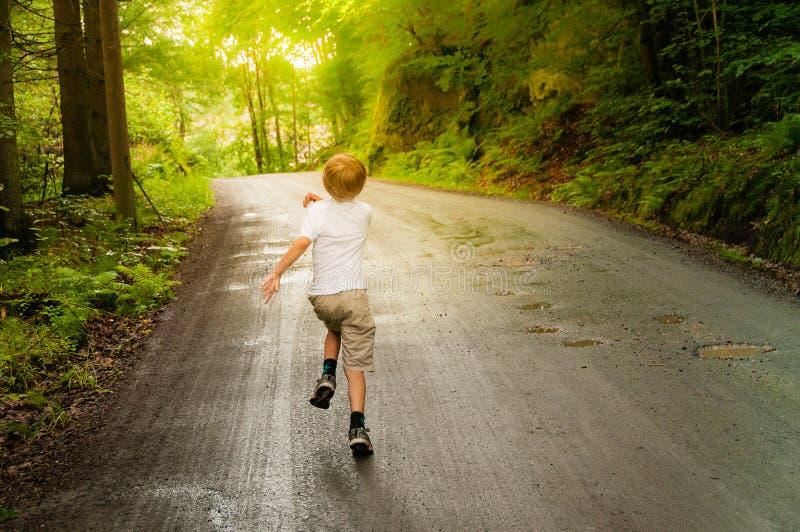 在森林里跑的年轻男孩 库存图片