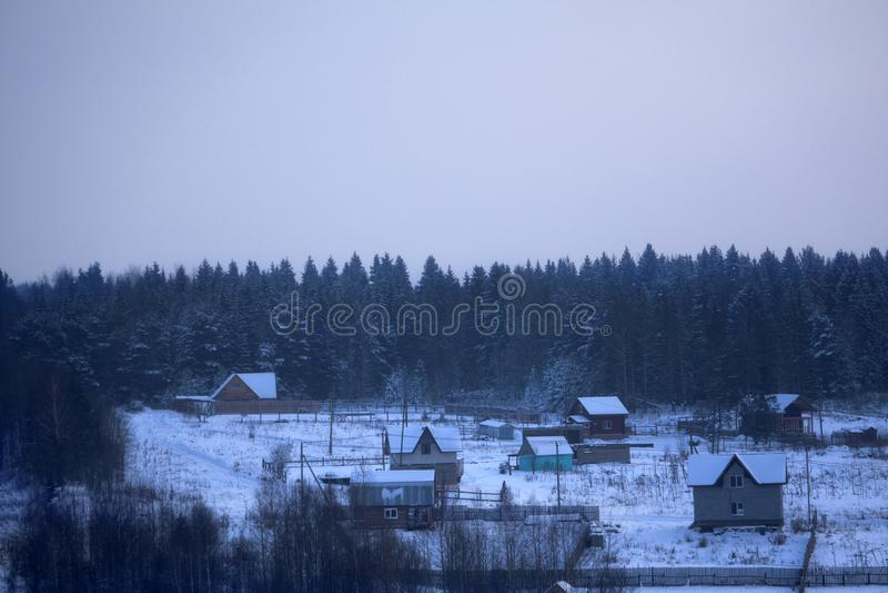 在森林附近的老被放弃的木小屋在晴朗的冬日在一点村庄在俄罗斯的斯摩棱斯克地区 免版税库存图片