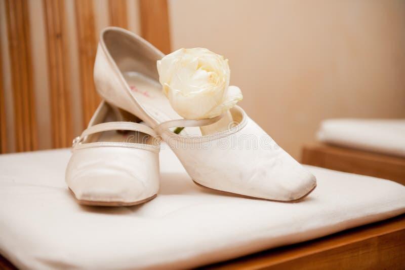 在椅子的新娘婚姻的鞋子与玫瑰 免版税库存照片