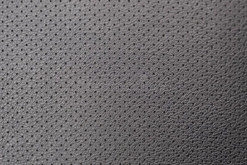 在椅子的被穿孔的皮革,黑皮革 库存图片