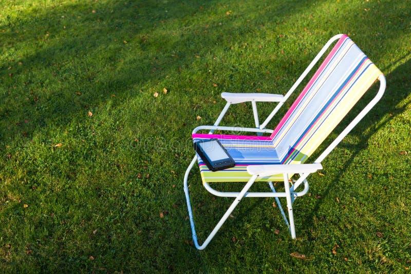 在椅子的E书读者,草背景 库存照片