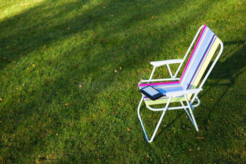 在椅子的E书读者,绿草背景 库存图片