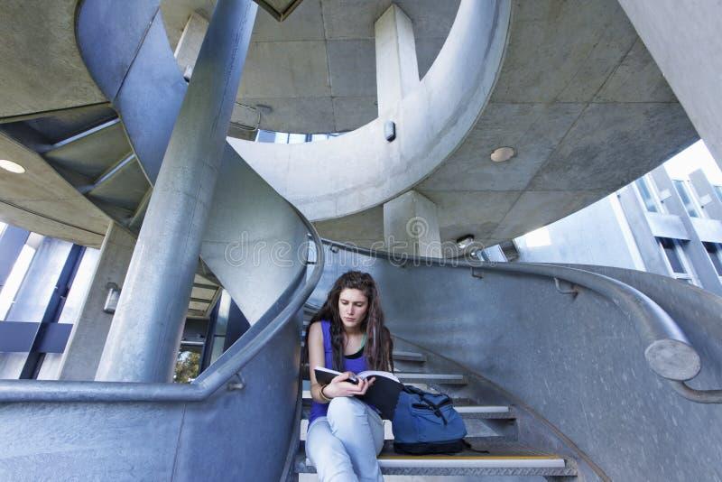 在楼梯的女学生读书 库存图片