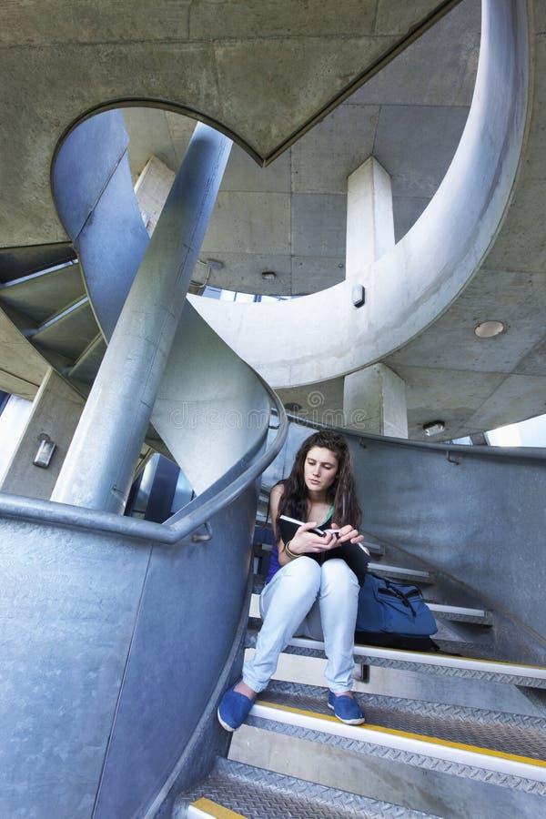 在楼梯的女学生读书 图库摄影