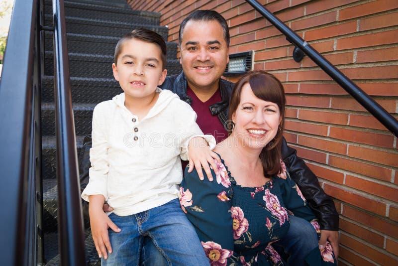 在楼梯的混合的族种年轻家庭画象 免版税库存图片