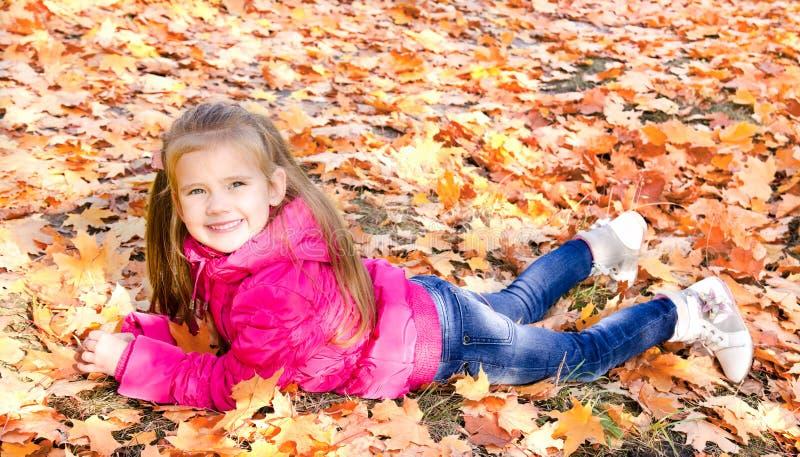 在槭树事假的逗人喜爱的微笑的小女孩秋天画象  免版税库存照片