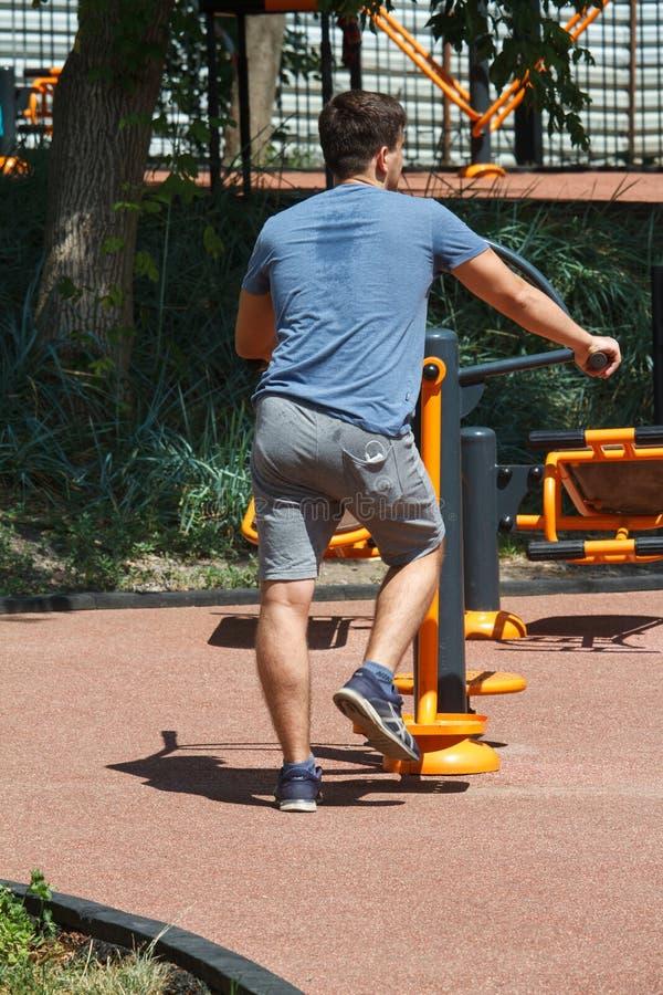 在模拟器的街道锻炼在一年轻人的城市公园一件满身是汗的T恤杉的 库存照片