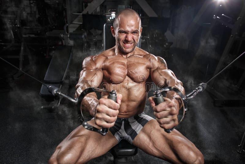 在模拟器的运动员肌肉爱好健美者训练胸口在健身房 免版税库存照片