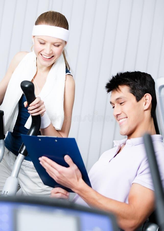 在模拟器的运动妇女训练在与教练的健身房 免版税图库摄影