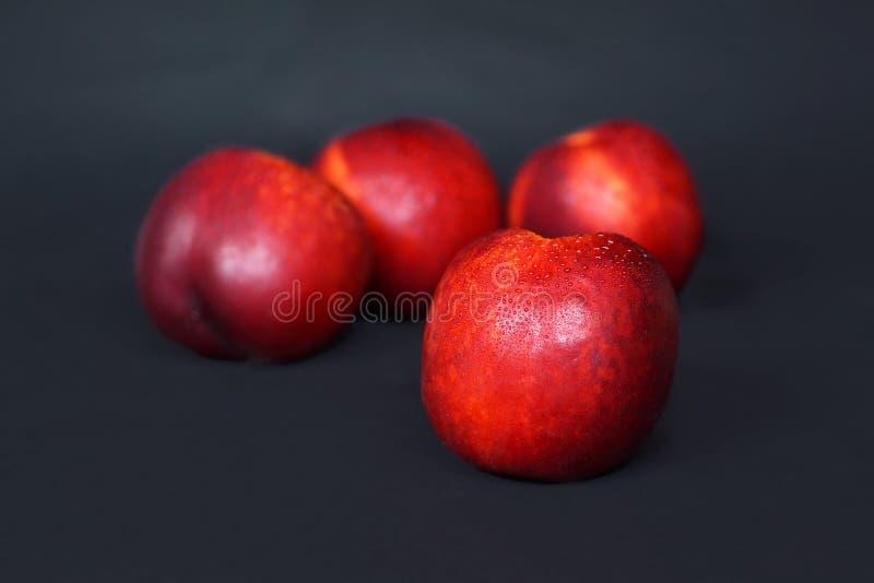 在模糊的果子前面的新鲜的成熟油桃在黑背景 库存照片