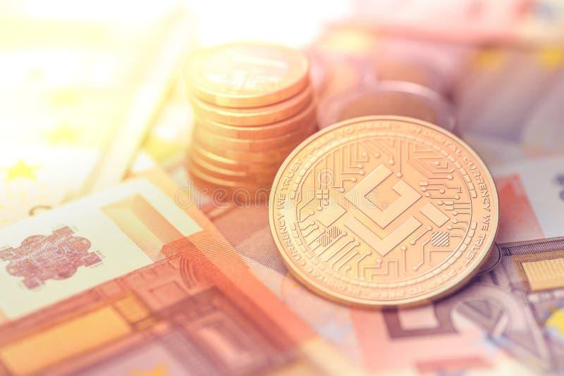 在模糊的背景的发光的金黄MOBILEGO cryptocurrency硬币与欧洲金钱 免版税库存照片