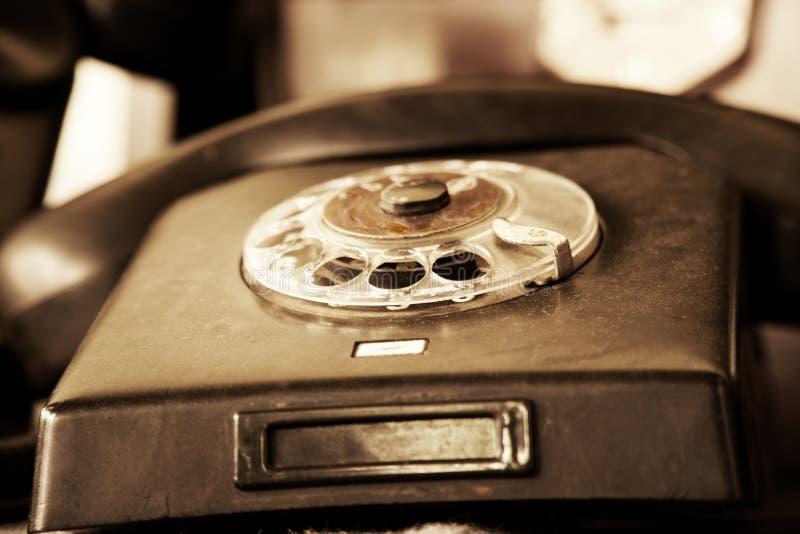 在模糊的背景的黑减速火箭的电话 减速火箭的办公室,在木桌上的电话静物画  库存图片