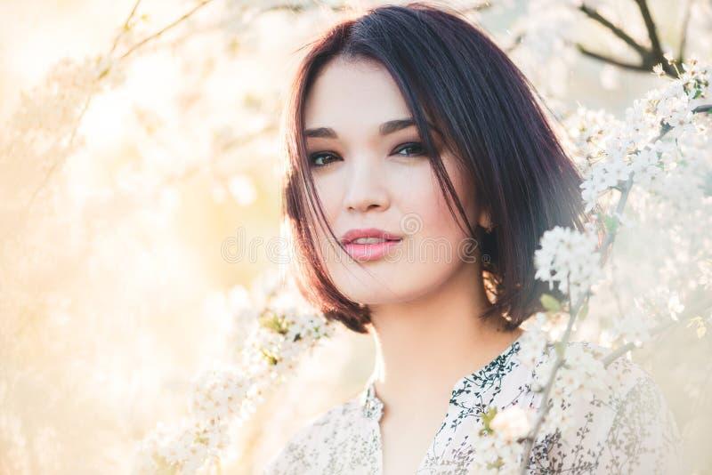 在樱桃佐仓开花中的美丽的中国女孩 免版税图库摄影
