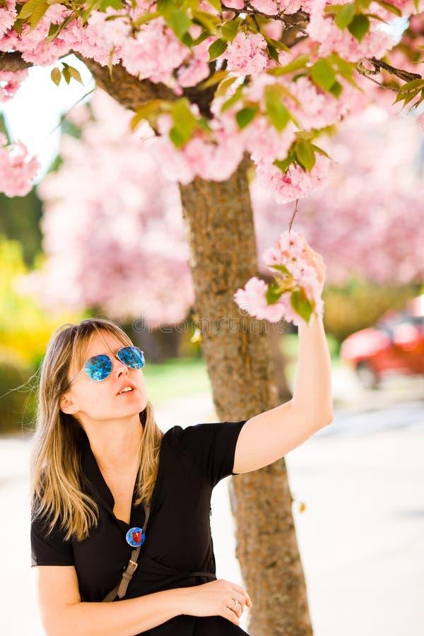 在樱花下的白肤金发的妇女 库存图片