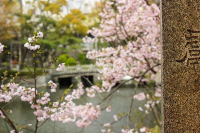 在樱花和石桥梁前面的石头日本标志 免版税图库摄影