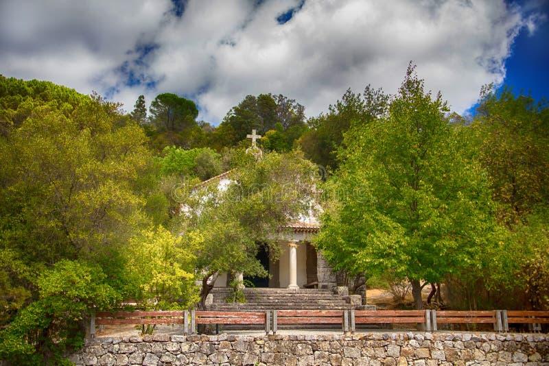 在橄榄树小树林的树中掩藏的一个小老教会 库存照片
