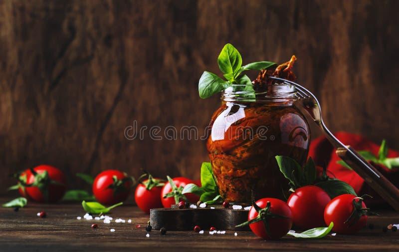 在橄榄油与绿色蓬蒿和香料的干蕃茄在木厨房用桌,土气样式,文本的地方上的玻璃瓶子 免版税库存图片