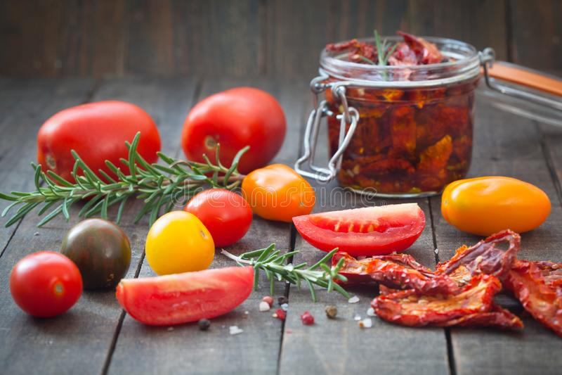 在橄榄油的各式各样的蕃茄用新鲜的草本、香料和海盐在一个玻璃瓶子 免版税图库摄影