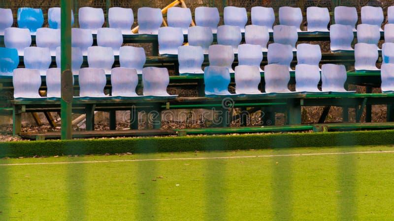 在橄榄球或足球场的草地和开放塑料的椅子的空的蓝色和白色位子 免版税库存图片