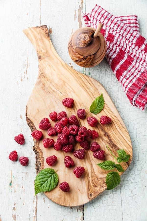 在橄榄色的木切板的莓 免版税库存照片