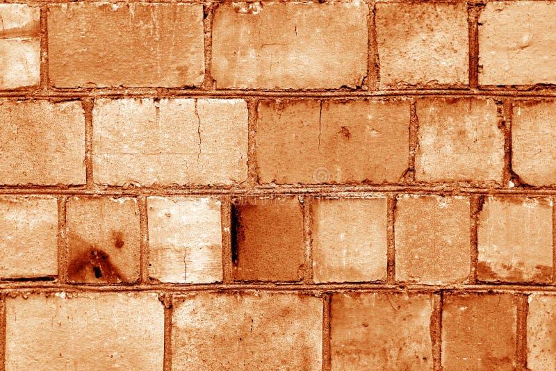 在橘黄色的老脏的砖墙表面 库存图片