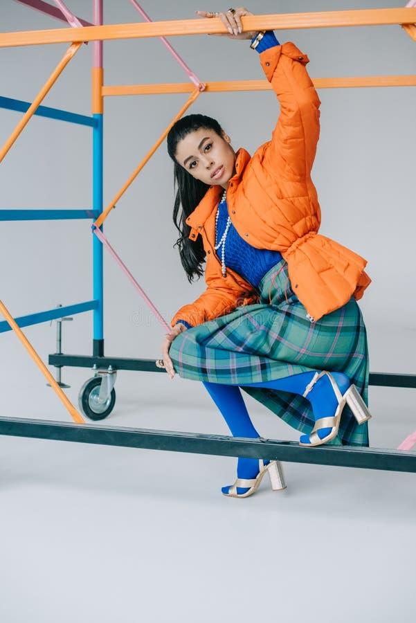 在橙色冬天夹克、方格的摆在五颜六色的绞刑台附近的裙子和蓝色贴身衬衣的时兴的非裔美国人的女性模型 免版税库存照片