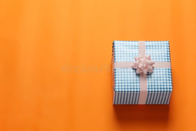 在橙色加工印刷纸地板和h安置的蓝色圣诞礼物箱子 免版税库存图片