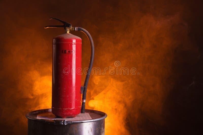 在橙色发烟性背景的灭火器 库存图片