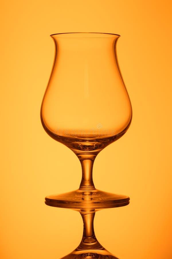 在橙色后面的清楚空的威士忌酒玻璃点燃了 库存图片