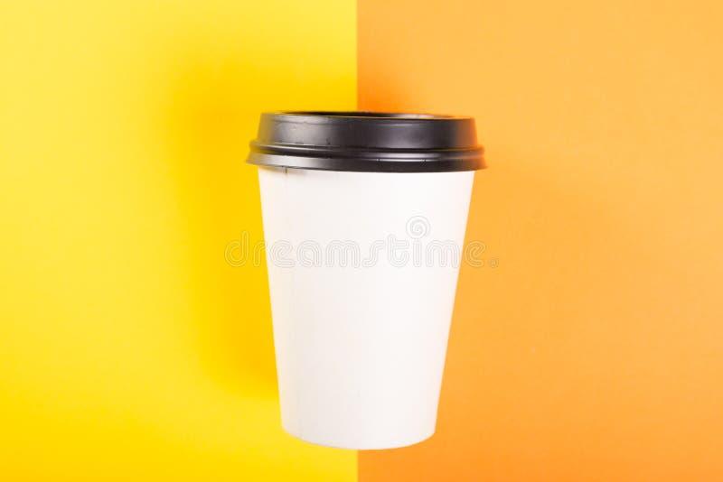 在橙色和黄色背景的外带的咖啡杯 免版税库存照片