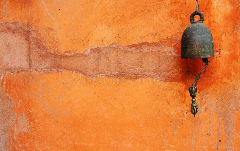 在橙色墙壁上的响铃 免版税图库摄影