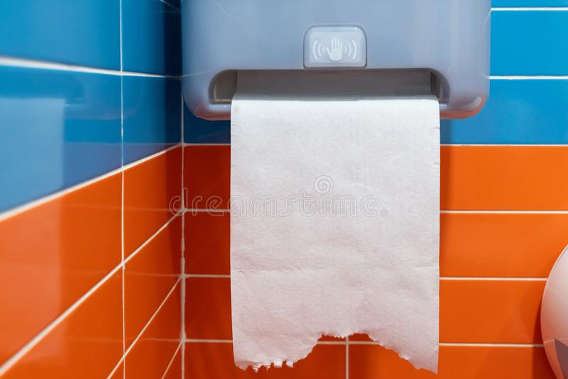 在橙色墙壁特写镜头的白色塑料毛巾纸分配器 图库摄影