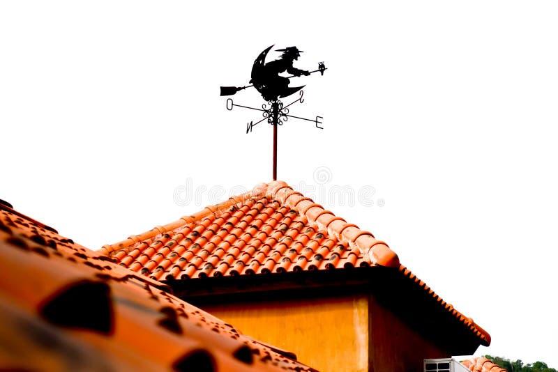 在橙色屋顶的查出的巫婆表单风向仪 库存图片