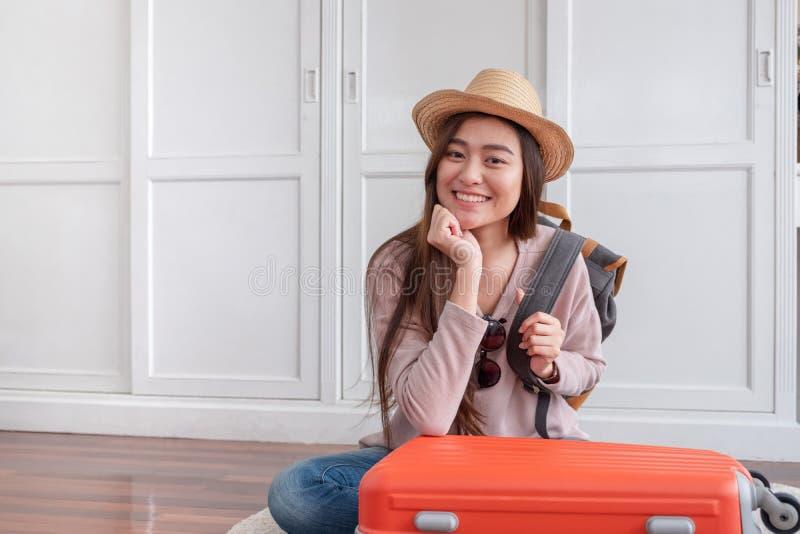 在橙色手提箱的年轻亚洲妇女旅客包装材料在家为假日假期做准备 背包徒步旅行者旅行概念 免版税库存照片