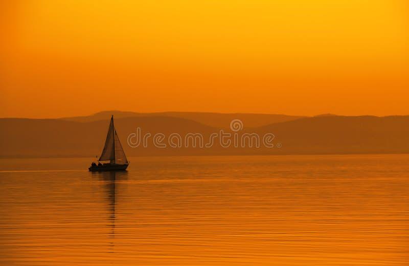 在橙色日落的帆船 免版税库存图片
