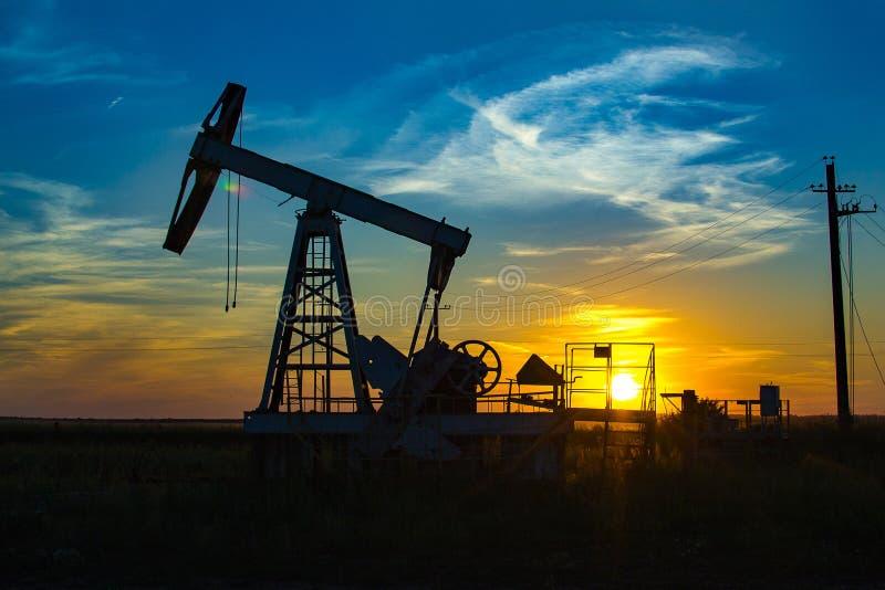 在橙色日落的油泵 图库摄影