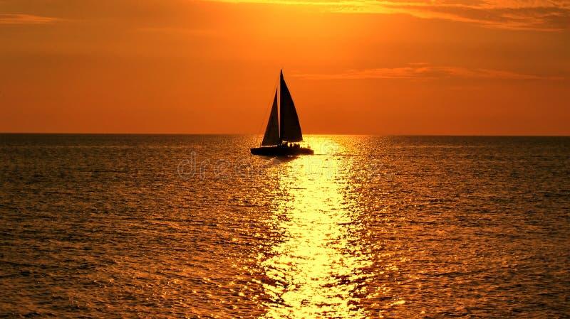 在橙色日落的游艇在海 免版税图库摄影
