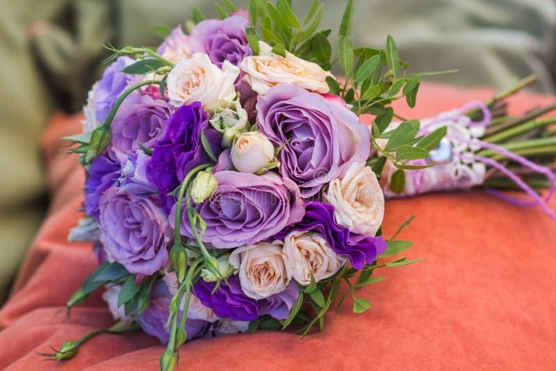 在橙色枕头的婚礼花束,新娘花束从玫瑰色奶油色浪花,玫瑰丛,玫瑰紫色回忆,紫罗兰色南北美洲香草, e的 库存照片