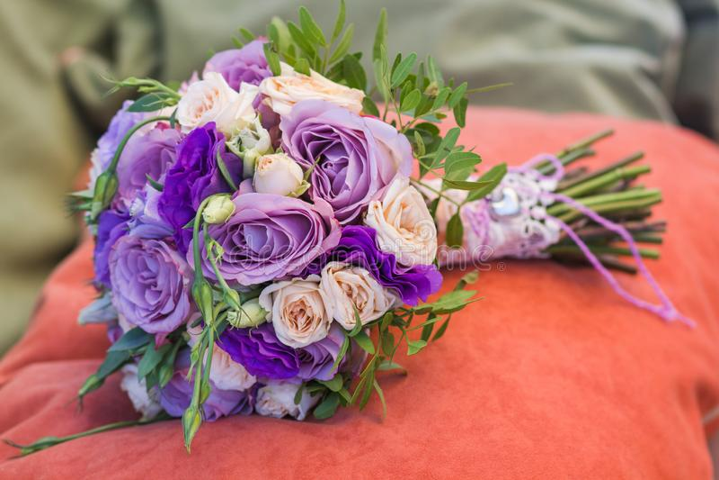 在橙色枕头的婚礼花束,新娘花束从玫瑰色奶油色浪花,玫瑰丛,玫瑰紫色回忆,紫罗兰色南北美洲香草, e的 库存图片
