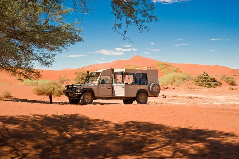 在橙色沙丘之间的徒步旅行队吉普在纳米比亚 风景在纳米比亚沙漠,纳米比亚 免版税库存图片