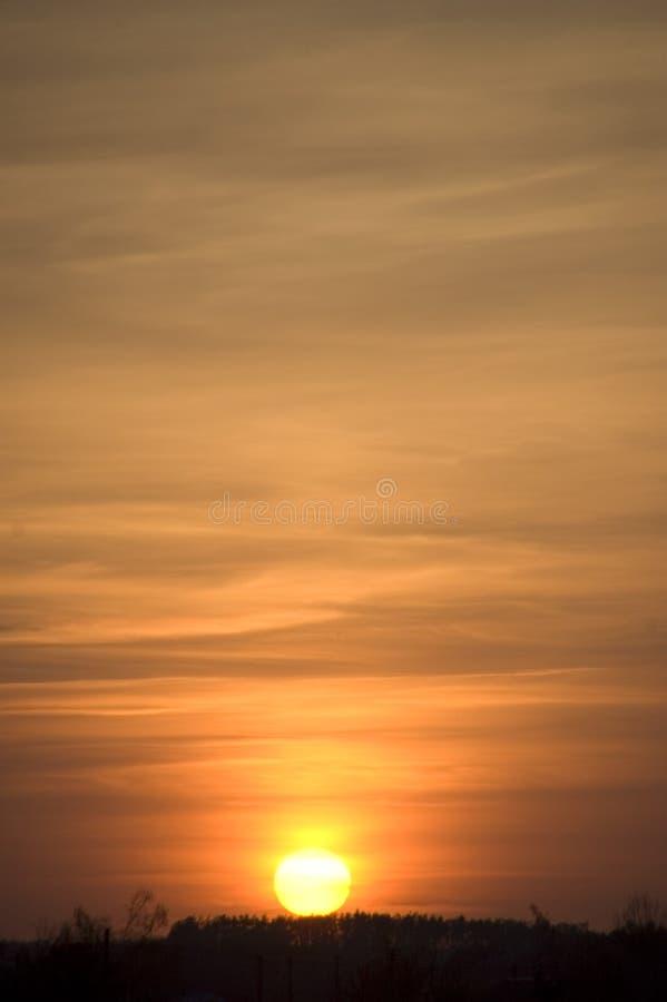 在橙色灰色相交的日落的橙色太阳 免版税库存图片