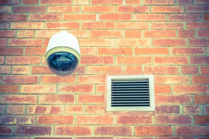 在橙色砖墙上的安全监控相机 免版税库存图片